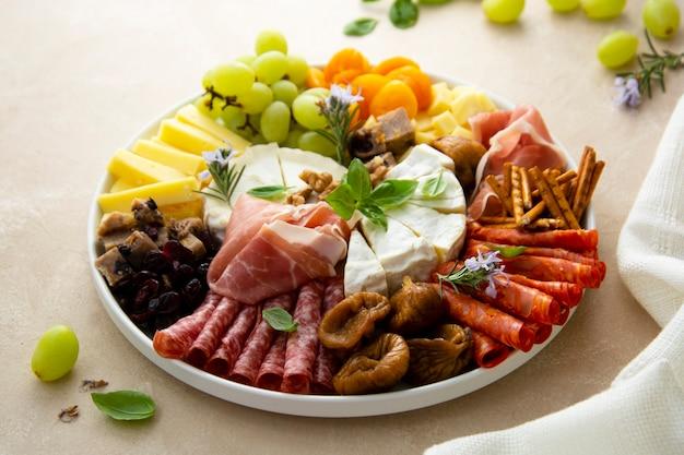 Charcuterie-assortiment, verschillende kazen en salami, prosciutto en gedroogde vruchten, vijgen, abrikozen, veenbessen. bovenaanzicht