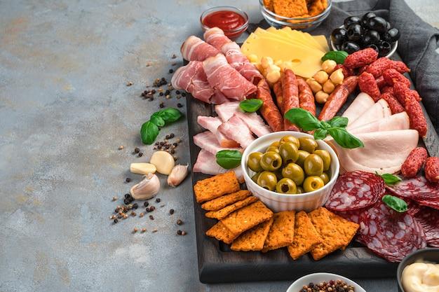 Charcuterie bord met verschillende soorten worst en kaas op een grijze achtergrond.