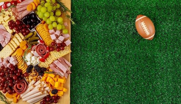 Charcuterie bord met voetbal bal op gras achtergrond. amerikaanse sport.