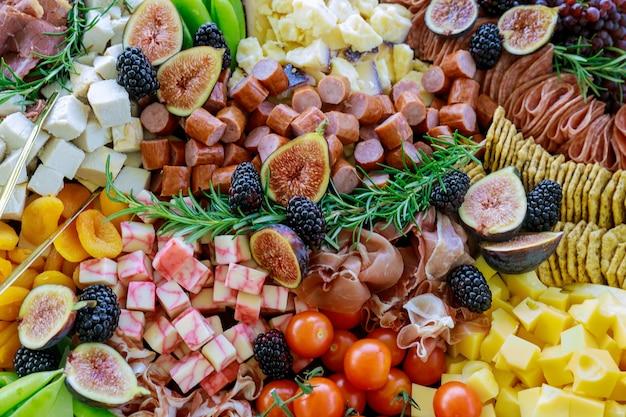 Charcuteriebord met een variëteit of assortiment van kaas, fruit en delicatessen. volledig frame.