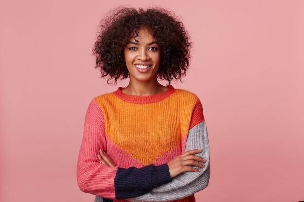 Charismatisch aantrekkelijk afrikaans amerikaans meisje met afro kapsel kijkt met plezier, met een aangename glimlach, sta met gekruiste armen, gekleed in kleurrijke longsleeve, geïsoleerd op roze muur