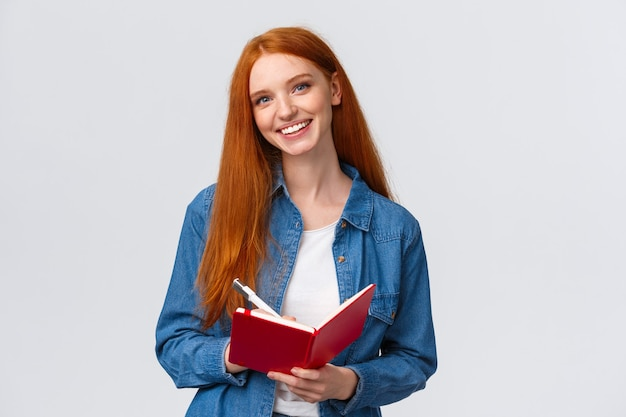 Charismatisch getalenteerde schattige roodharige vrouwelijke student studeert, notities maken na leraar in notitieblok