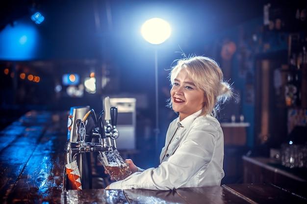 Charismatisch meisje barman maakt een show en maakt een cocktail aan de bar