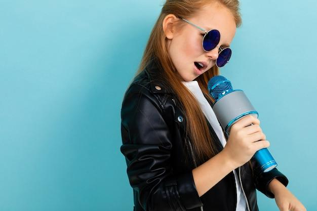 Charismatisch mooi schoolmeisje met een microfoon in haar handen danst en zingt tegen een blauwe muur