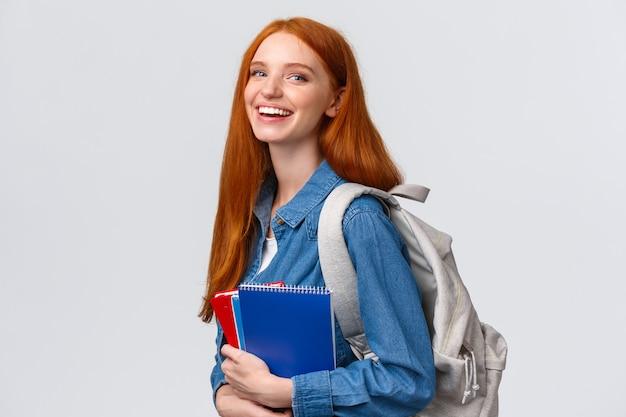 Charismatisch roodharige meisje met rugzak, notebooks en studieboeken