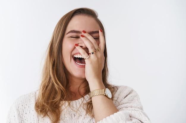 Charismatisch zorgeloos vrolijk vriendelijk kijken uitgaande vrouw houdt van hardop lachen niet verbergen emoties giechelen hoor grappig hilarische grap grinniken facepalm ogen sluiten glimlachend breed witte achtergrond