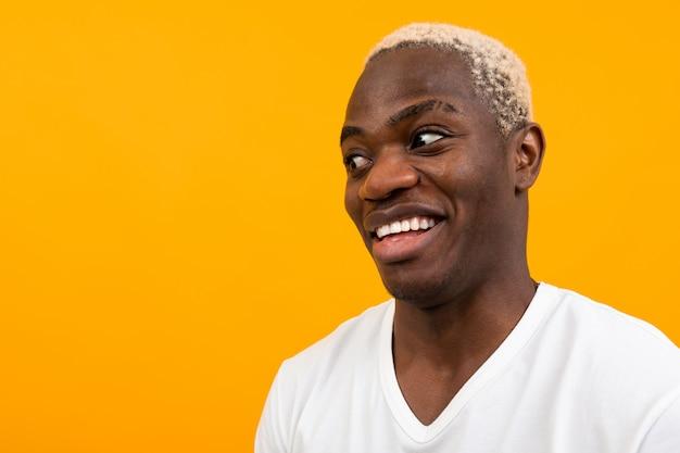 Charismatische afrikaanse man in een wit t-shirt kijkt verbaasd aan de zijkant op geel met kopie ruimte