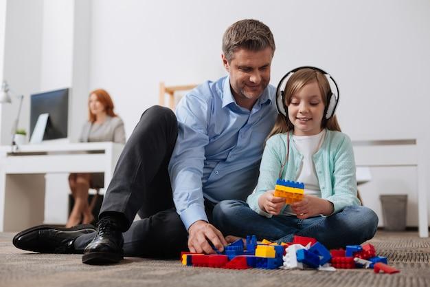 Charismatische, attente liefdevolle vader die zijn kind vermaakt terwijl hij haar met hem naar kantoor brengt
