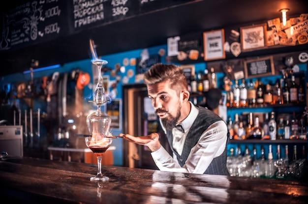 Charismatische bartending demonstreert zijn vaardigheden over de toonbank achter de bar