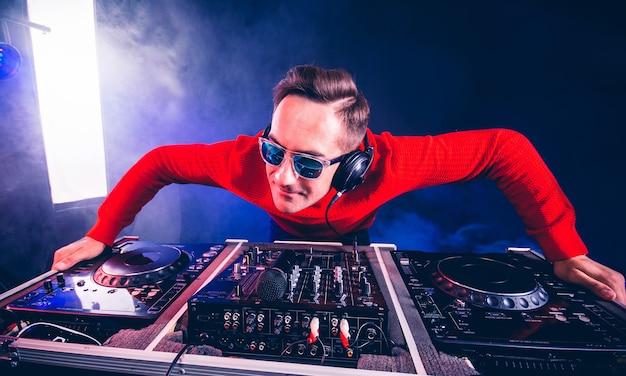 Charismatische dj die boven de muziekcontrole van de draaitafel zweeft in de nachtclub.