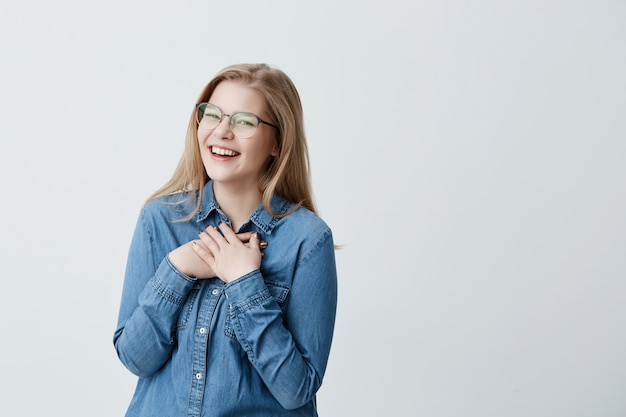 Charismatische en charmante jonge europese vrouw met steil blond haar die een stijlvolle bril en een spijkerblouse draagt, wijd glimlachend, in afwachting van verrassing kijkend, gelukkig uitziend