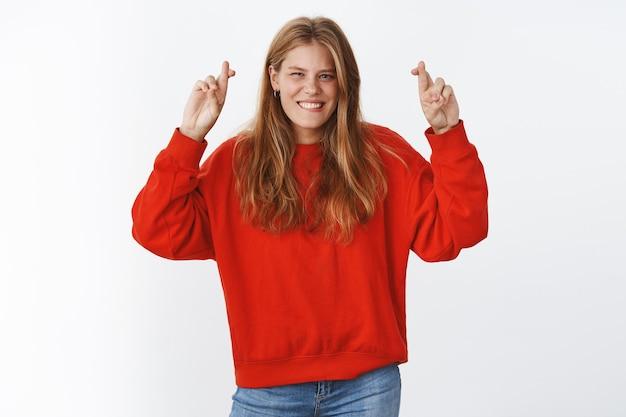 Charismatische en optimistische jonge europese vrouw in rode oversized trui die handen met gekruiste vingers opsteekt voor geluk glimlachend in het algemeen geluk en geluk aan haar zijde, geloof in overwinning en succes