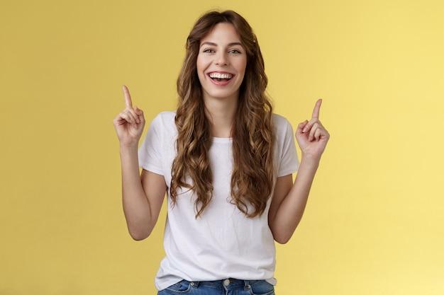 Charismatische enthousiaste aantrekkelijke levendige vrouw die plezier heeft geniet van een geweldig avondje uit feest lachen vreugdevol omhoog wijzende wijsvingers omhoog introduceren promo glimlachend gelukkig gele achtergrond