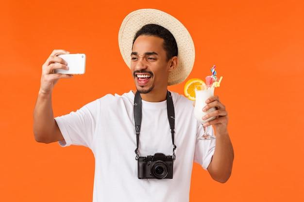 Charismatische, enthousiaste grappige jonge afro-amerikaanse man die lacht, juicht en alcohol drinkt, selfie neemt, fotografeert, camera vasthoudt, toerist op zomervakantie