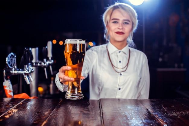Charismatische meisjesbarkeeper maakt een show en maakt een cocktail achter de bar