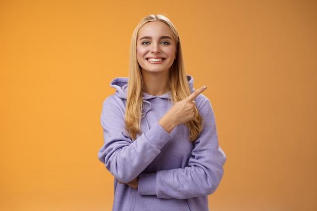 Charismatische moderne duizendjarige schattige blonde vrouw in hoodie glimlachend gelukkig bespreken coole nieuwe promo rechts aan te bevelen check out bezoek interessante winkel in de buurt van hoek, oranje achtergrond.