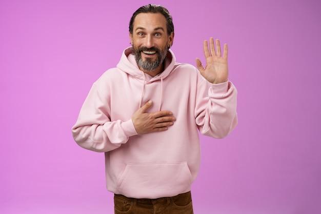 Charismatische oprechte optimistische gelukkige europese volwassen 40s man met baard smeken vloeken vertellen waarheid houden hand hart verhogen palm maken belofte vreugdevol, staande paarse achtergrond glimlachend witte tanden.