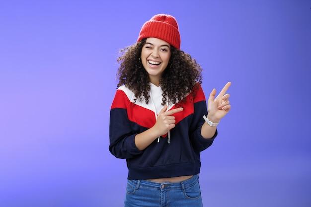 Charismatische speelse jonge europese vrouw met krullend haar die vrolijk naar de camera knipoogt terwijl ze naar de rechterbovenhoek wijst met een hoed en pullover als blij poserend over een blauwe achtergrond, zich warm voelend.