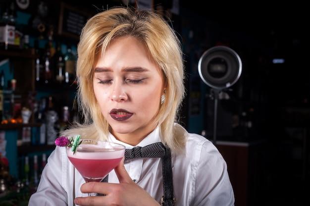 Charismatische vrouw barman maakt een cocktail in de nachtclub