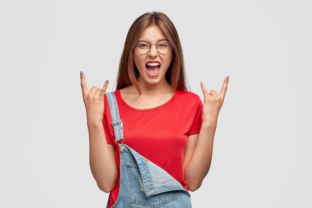 Charismatische vrouw met aantrekkelijke uitstraling, toont rock n roll-gebaar, roept met plezier uit