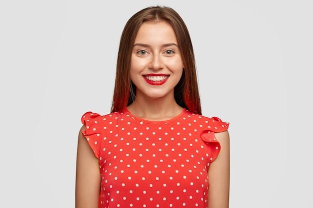Charismatische vrouw met rode lippenstift poseren tegen de witte muur