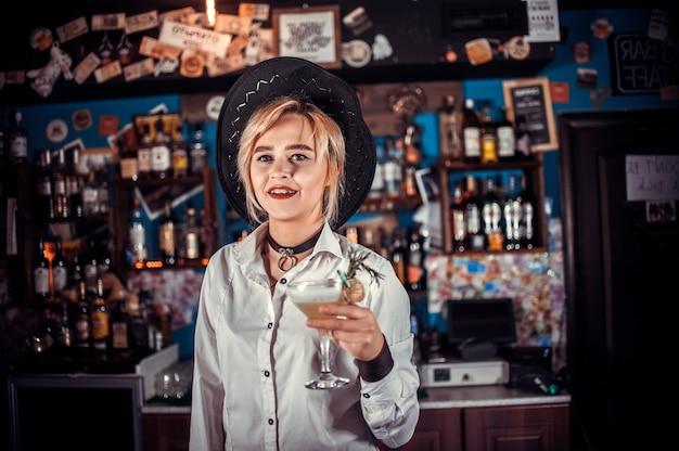Charismatische vrouwenbartending demonstreert het proces van het maken van een cocktail