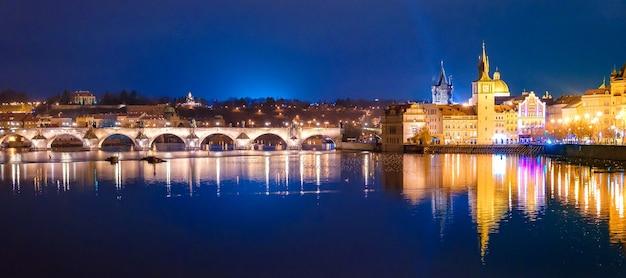 Charles bridge en karlovy lazne bij nachtlichten in praag, tsjechische republiek.