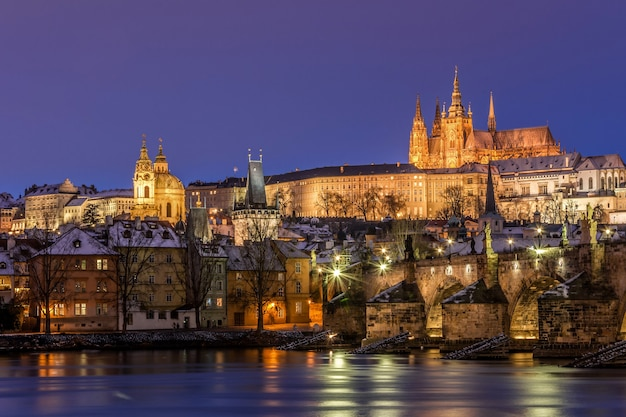 Charles bridge en prague castle in praag tijdens zonsondergang met nachtverlichting