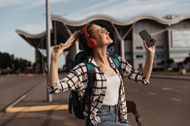 Charmant blond meisje in zonnebril, rode koptelefoon luistert naar muziek