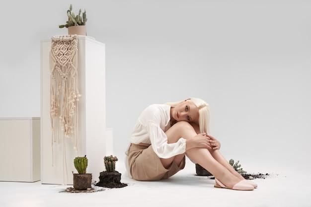 Charmant blond meisje met mooie make-up in witte blouse, beige korte broek en ballet flats, zittend op de vloer van witte studio met gebroken potten met groene cactus. concept van natuur en schoonheid