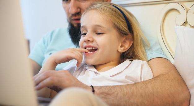 Charmant blond meisje tijd doorbrengen met haar bebaarde vader liggend op de bank en iets te lezen