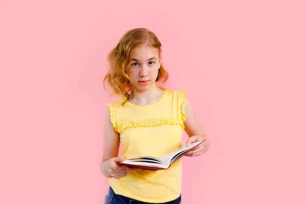 Charmant blondemeisje in het gele t-shirt stellen met schriften