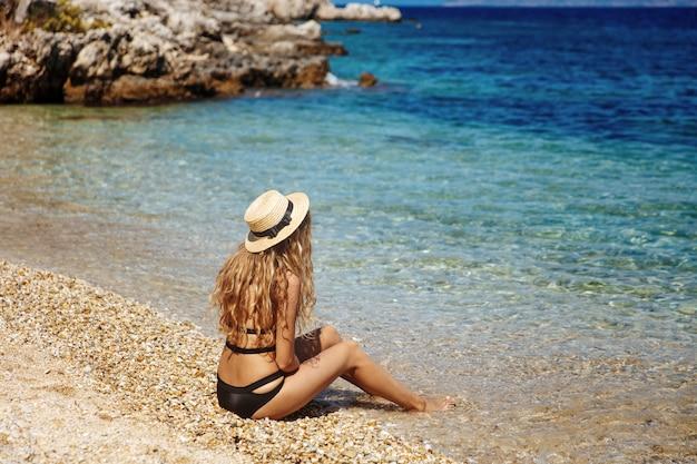 Charmant blondemeisje in zwarte bikini die op het strand zonnebaadt