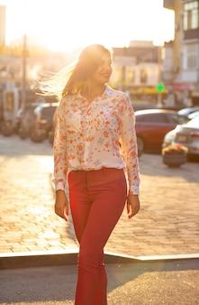 Charmant brunette model in kostuum en blouse poseren met zacht avondzonlicht