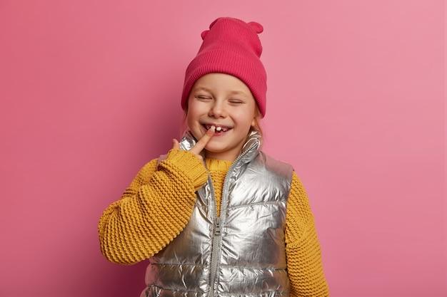 Charmant dochtertje, vrouwelijk kindje wijst naar haar nieuwe tand, glimlacht breed, draagt hoed, gebreide trui en vest, voorkomt cariës, geeft om tanden, modellen over pastelroze muur