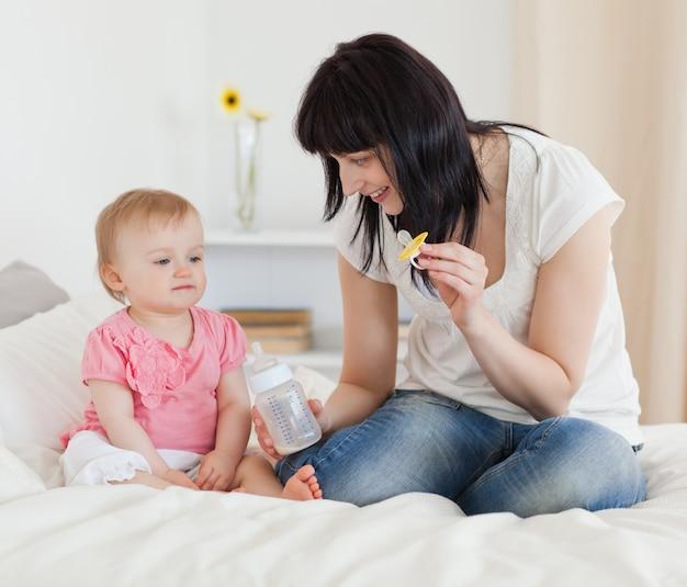 Charmant donkerbruin wijfje dat een het voeden fles aan haar baby toont terwijl het zitten op een bed