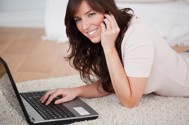 Charmant donkerbruin wijfje op de telefoon terwijl het ontspannen met haar laptop
