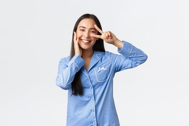 Charmant dwaas aziatisch meisje in blauwe jammies die vredesteken tonen en wangkawaii aanraken, blozen en glimlachen, tevreden met schone perfecte huid, huidverzorgingsproducten gebruiken, witte achtergrond.