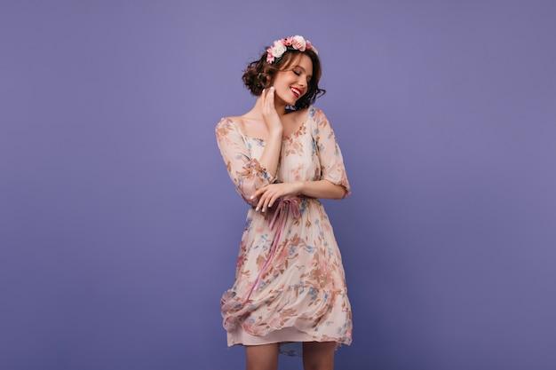 Charmant europees meisje in korte jurk staan. kortharige dame in bloemenkrans.