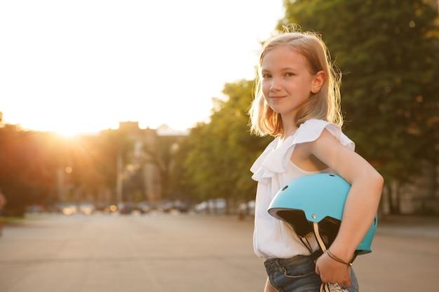 Charmant gelukkig jong meisje glimlachend naar de camera, met beschermende helm buitenshuis