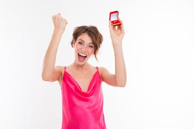 Charmant gelukkig meisje in een roze jurk met een doos met een trouwring zegt ja op een witte muur