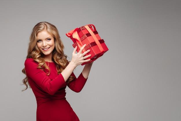 Charmant gelukkig meisje met rode dozen met rode boog.