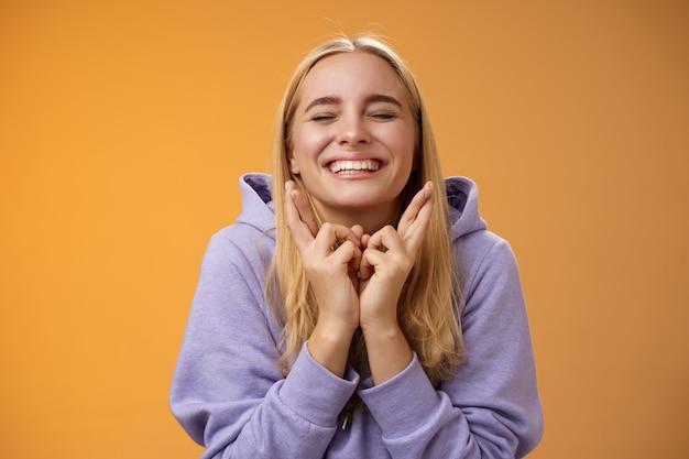 Charmant gelukkig schattig jong gelukkig hoopvol blond meisje sluit ogen lachend positief kruis vingers veel geluk wil winnen trouw bidden maak wens verlangen droom uitkomen, staande oranje achtergrond.