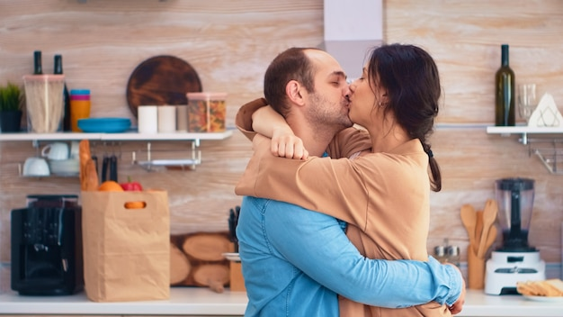 Charmant getrouwd stel vol geluk dansen in de keuken. vrolijke gelukkige jonge familie dansen samen. leuke liefde genegenheid romantiek vrije tijd romantische muziek om van te genieten