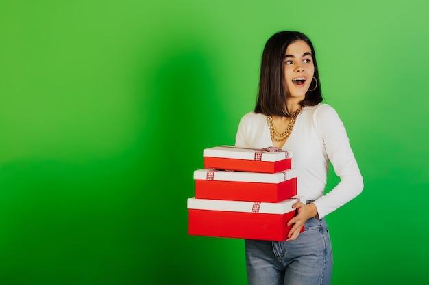 Charmant glimlachend gelukkig meisje dat heel wat geschenkdozen houdt, geïsoleerd op groen oppervlak.