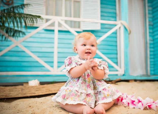 Charmant glimlachend meisje in een bloemenjurk zit op het zand tegen de achtergrond van een blauw landhuis.