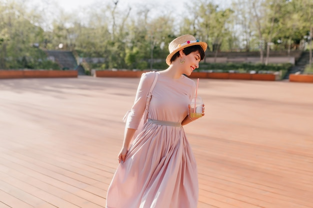 Charmant glimlachend meisje met kort zwart haar met plezier op houten dansvloer in park