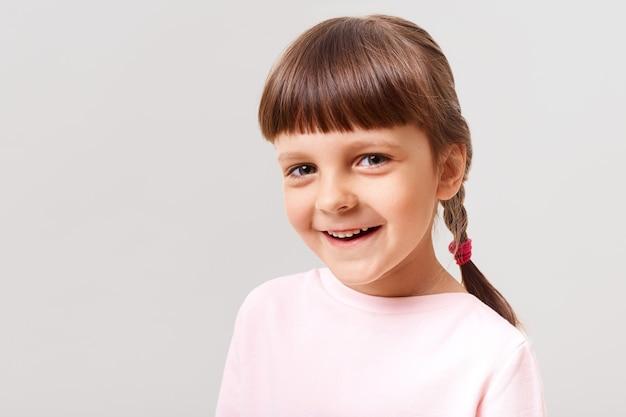 Charmant glimlachend vrouwelijk kind dat roze sweater draagt die voorzijde met gelukkige uitdrukking bekijkt