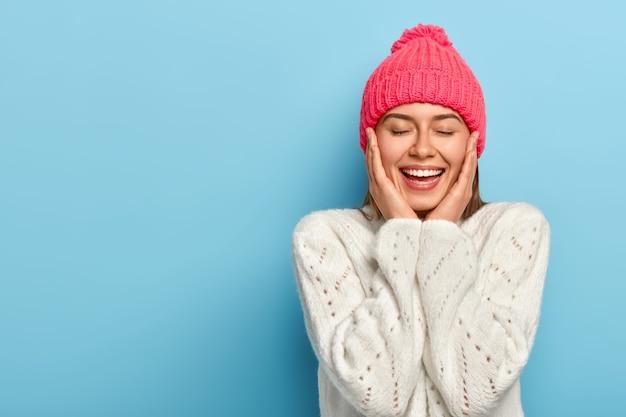 Charmant glimlachend vrouwelijk meisje raakt wangen met beide handen, ogen dicht, brede verleidelijke glimlach, draagt witte wintertrui, poseert tegen blauwe studiomuur, heeft een pure gezonde huid, voelt zich opgelucht