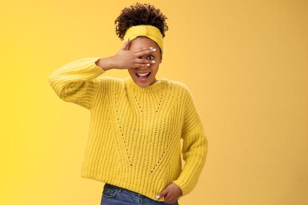 Charmant hartstochtelijk gelukkig lachend afro-amerikaans millennial meisje verbergt ogen hand op gezicht gluurt door vingers vrolijk grijnzend genietend van wat ziet kan niet meer tegenhouden wil verrassing zien.